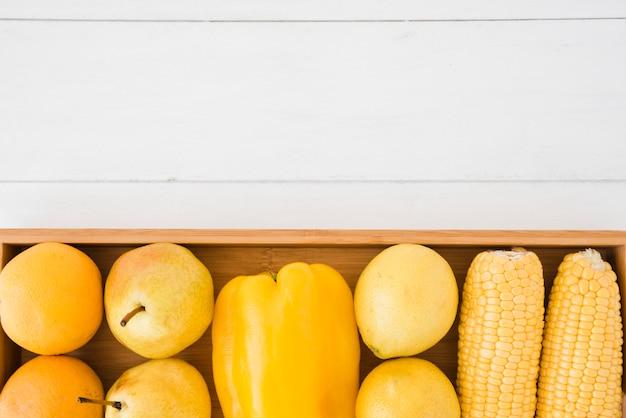 Ogólny Widok Pomarańczy; Gruszki; Papryka; Cytryna I Kukurydza Na Drewnianej Tacy Nad Białym Biurkiem Darmowe Zdjęcia
