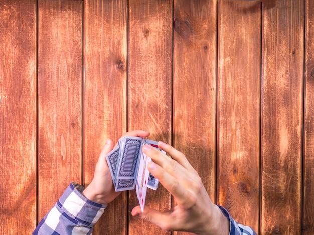 Ogólny Widok Rąk Mieszania Kart Do Gry Na Powierzchni Drewnianych Premium Zdjęcia