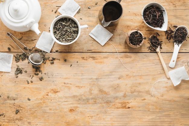 Ogólny widok suchych liści herbaty; czajniczek; sitko do herbaty; torebka i łyżka na drewnianym stole Darmowe Zdjęcia