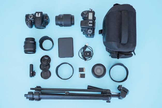 Ogólny widok torby i urządzenia do fotografii na niebieskim tle Darmowe Zdjęcia