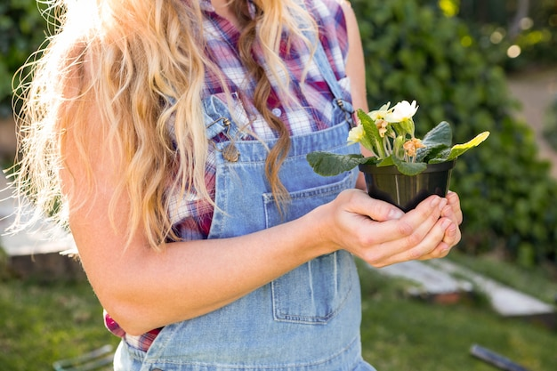 Ogrodniczki kobieta trzyma kwiaty w ogródzie Premium Zdjęcia