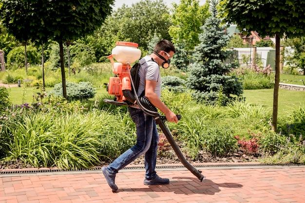 Ogrodnik W Masce Ochronnej I Okularach Rozpylających Toksyczne Pestycydy Drzew Premium Zdjęcia