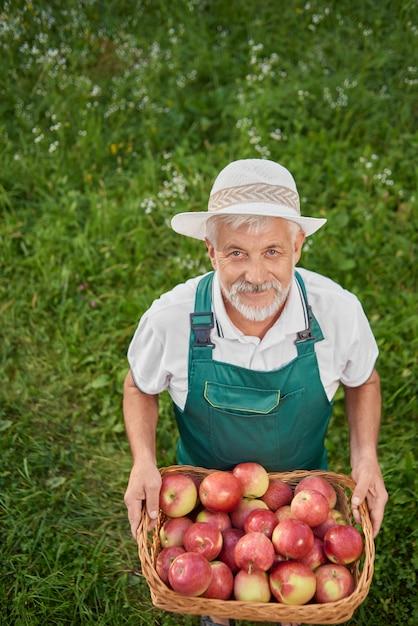 Ogrodnik W Zielonym Gospodarstwie Kosz Pełen świeżych Czerwonych Jabłek. Premium Zdjęcia