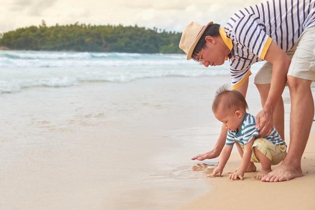 Ojciec Bawi Się Piaskiem Ze Słodkim Azjatyckim 18-miesięcznym Dzieckiem Chłopca Na Białej, Piaszczystej Plaży, Letnie Wakacje Na Plaży Z Dziećmi, Zabawa Sensoryczna Z Koncepcją Piasku Premium Zdjęcia