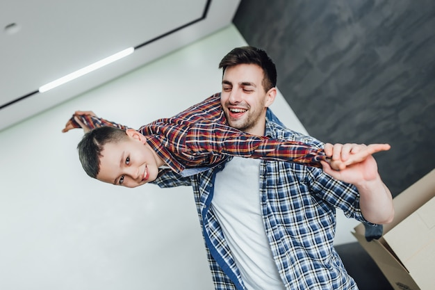 Ojciec bawi się z synem w nowym nowoczesnym domu wesoły emocje poranny weekend w ruchu Premium Zdjęcia