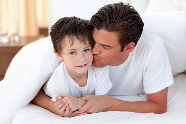 Ojciec Całuje Jego Syna Lying On The Beach Na łóżku Premium Zdjęcia