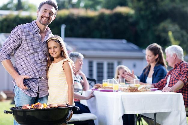 Ojciec i córka na grilla, podczas gdy rodzina obiad Premium Zdjęcia