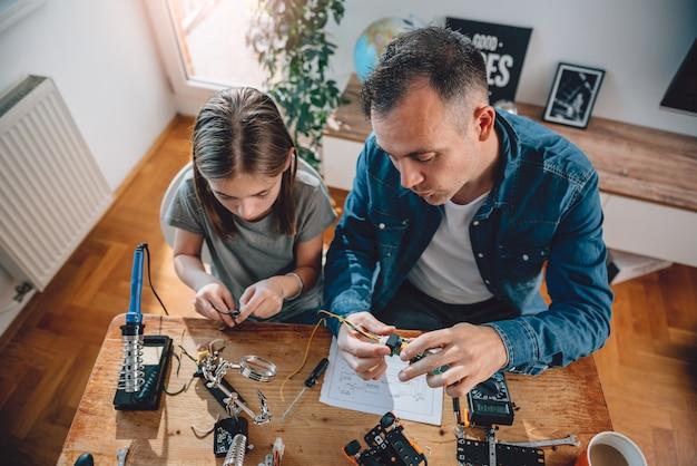 Ojciec i córka pracuje na komponentach elektronicznych Premium Zdjęcia