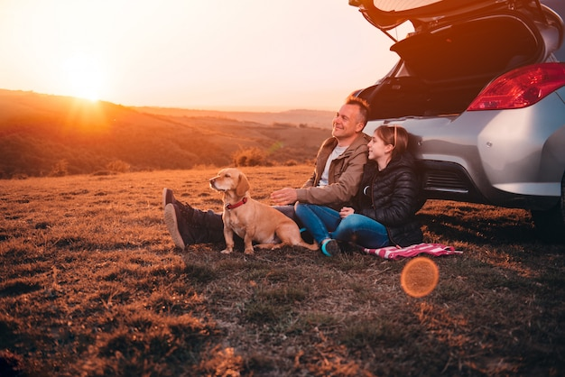 Ojciec i córka z psem obozuje na wzgórzu samochodem podczas zmierzchu Premium Zdjęcia