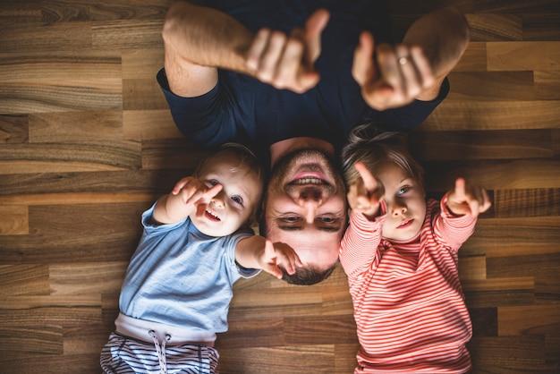 Ojciec i dziecko leżące na podłodze z podniesionymi rękami Darmowe Zdjęcia