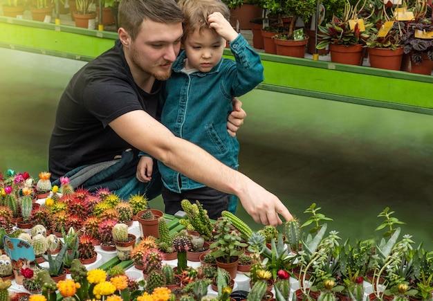 Ojciec I Jej Synek W Sklepie Z Roślinami, Patrząc Na Kaktusy. Ogrodnictwo W Szklarni. Ogród Botaniczny, Hodowla Kwiatów Premium Zdjęcia