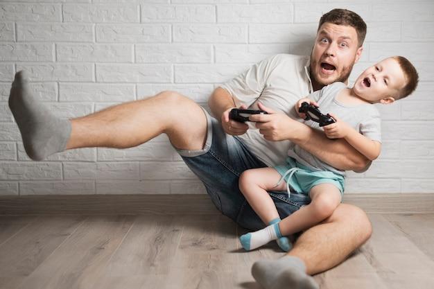 Ojciec i mały chłopiec bawi się ze swoimi kontrolerami Darmowe Zdjęcia