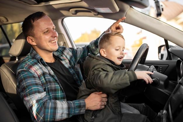 Ojciec I Syn Bawiący Się Kierownicą Samochodu Darmowe Zdjęcia