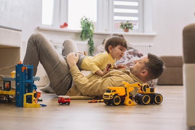 Ojciec I Syn Bawić Się Na Podłogowym Długim Strzale Darmowe Zdjęcia