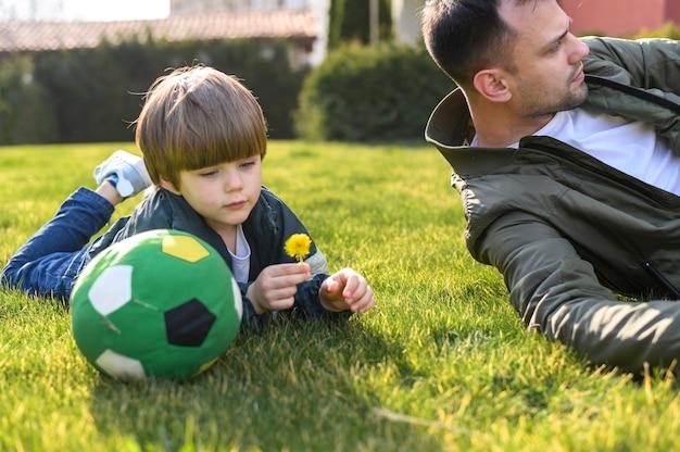 Ojciec I Syn Kłaść Na Trawie Darmowe Zdjęcia