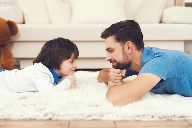 Ojciec i syn leży na dywanie w domu. Premium Zdjęcia