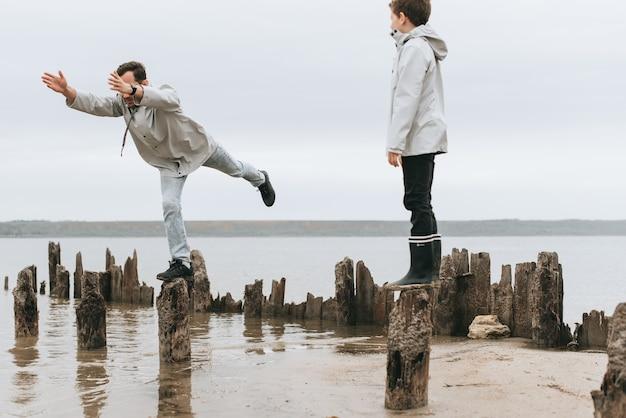 Ojciec i syn mają świetną zabawę i robią ćwiczenia joga w deszczu koło morza Premium Zdjęcia