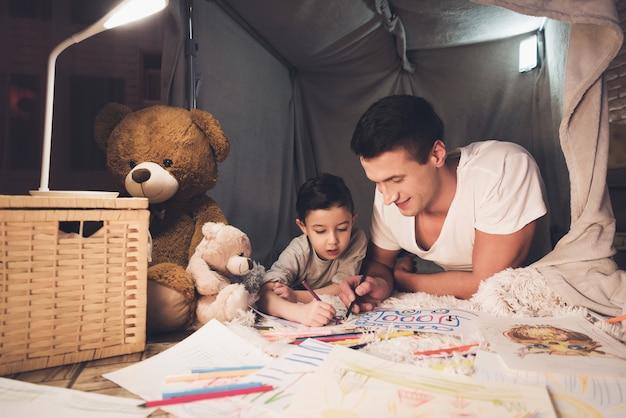 Ojciec i syn rysują kredkami na papierze. Premium Zdjęcia