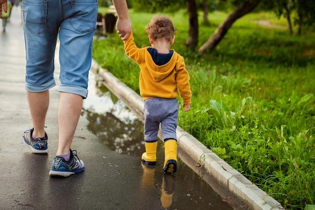 Ojciec I Syn Spacery świeżym Powietrzem W Gumowe Buty Na Kałużach Po Deszczu W Letni Dzień. Małe Dziecko Trzyma Rękę Mężczyzny. Premium Zdjęcia