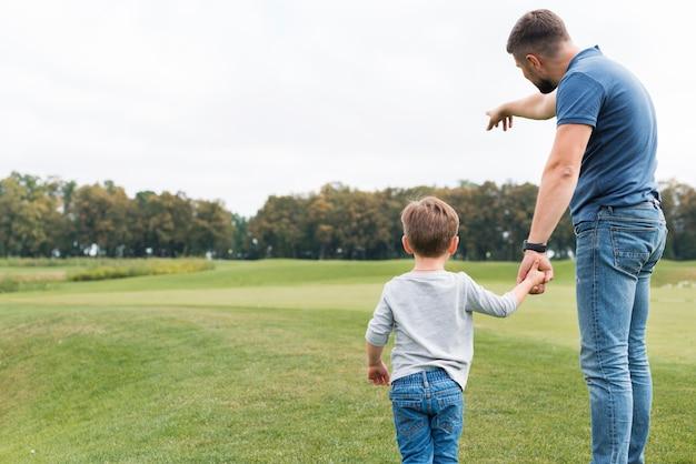 Ojciec I Syn Trzymając Się Za Ręce Od Tyłu Strzału Darmowe Zdjęcia