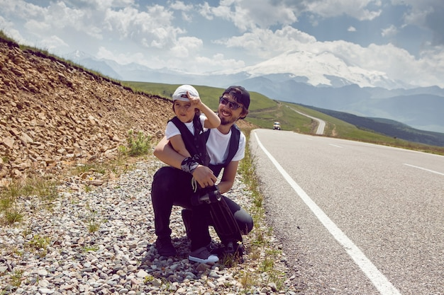 Ojciec I Syn W Czapkach I Okularach Przeciwsłonecznych łapią Samochód Stojący Na Drodze W Górach Premium Zdjęcia