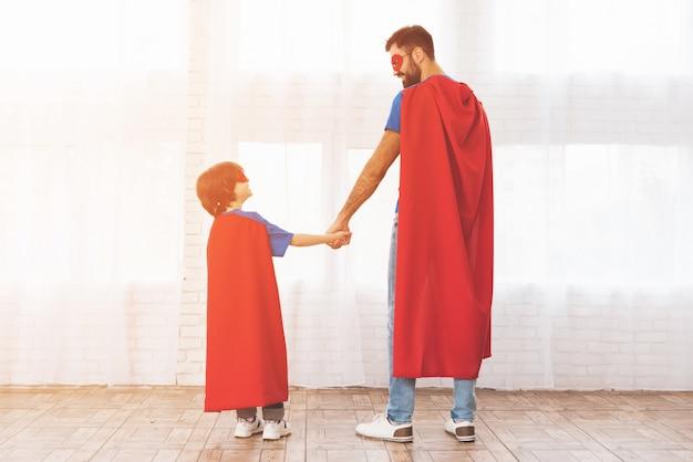 Ojciec i syn w czerwonych i niebieskich garniturach superbohaterów. Premium Zdjęcia