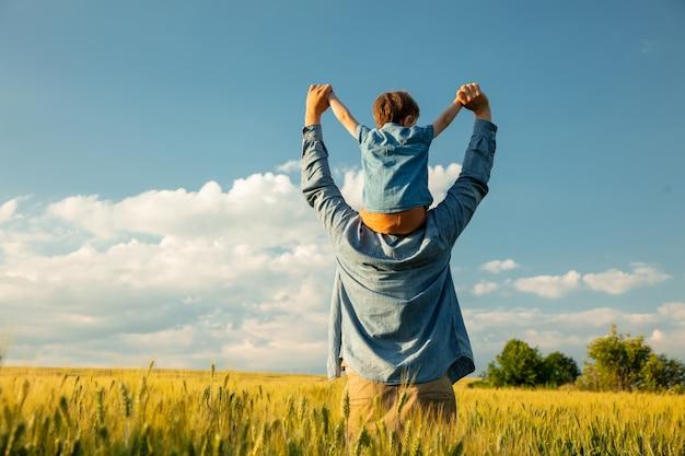 Ojciec I Syn W Polu Pszenicy, Dziecko Siedzi Na Ramionach Ojców Premium Zdjęcia