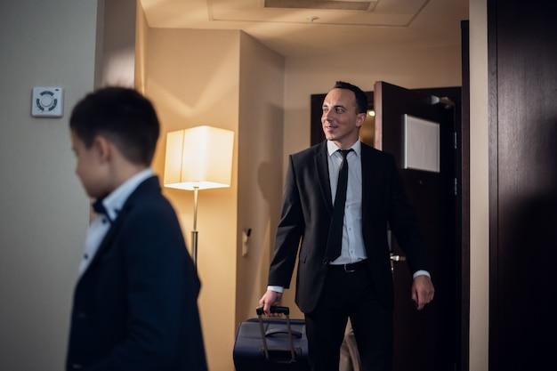Ojciec I Syn W Strojach Wizytowych Wchodzących Do Pokoju Hotelowego, Ojciec Niesie Dużą Walizkę Premium Zdjęcia