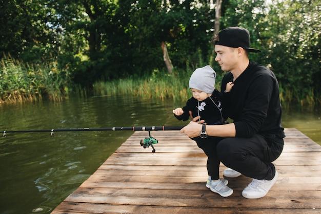 Ojciec I Uroczy Roczny Syn łowiący Wędkę W Naturze. Koncepcja Ucieczki Na Wsi. Artykuł O Dniu Połowów. Premium Zdjęcia