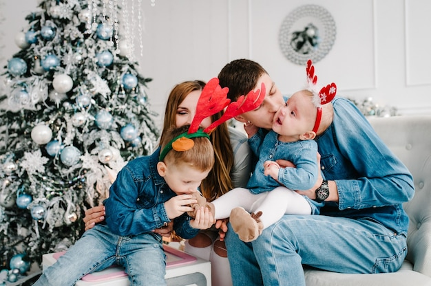 Ojciec, Matka Trzyma Synka I Córkę W Pobliżu Choinki Premium Zdjęcia