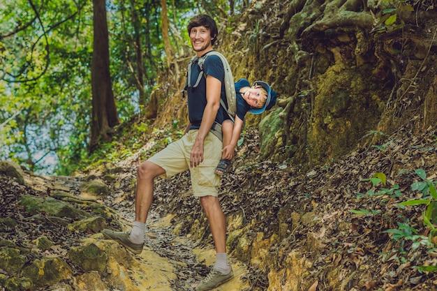 Ojciec Niesie Syna W Noszeniu Dziecka, Wędruje Po Lesie. Premium Zdjęcia