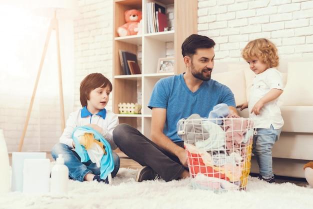 Ojciec Pokazuje Dzieciom, Jak Posprzątać Dom. Premium Zdjęcia