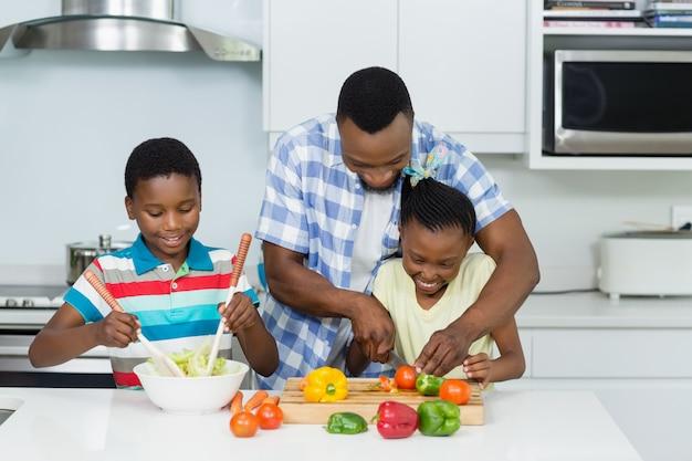 Ojciec Pomaga Dzieciom W Przygotowaniu Sałatki W Kuchni Premium Zdjęcia