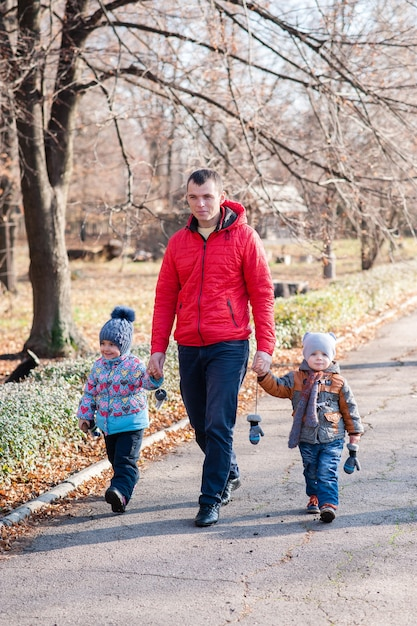 Ojciec Z Dziećmi Spacerujący Po Parku Premium Zdjęcia