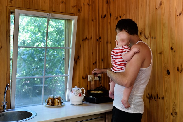 Ojciec z małym dzieckiem w ramionach gotuje obiad. wnętrze wiejskiego domu Premium Zdjęcia