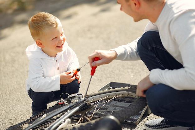 Ojciec Z Synem Naprawia Rower W Parku Darmowe Zdjęcia