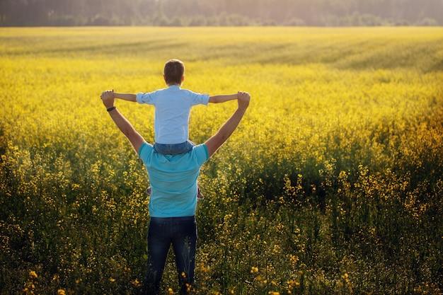 Ojcuje trzymać jego syna na ramionach i pozycja na natury lata tle. Premium Zdjęcia