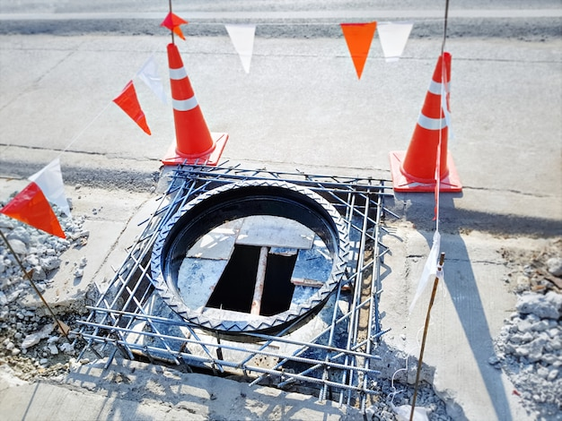 Okrągły Właz Kanalizacyjny W Budowie Ze Stożkami Drogowymi Jako Barykada Ostrzegawcza Premium Zdjęcia