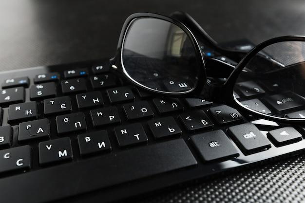 Okulary I Klawiatura Na Stole Premium Zdjęcia