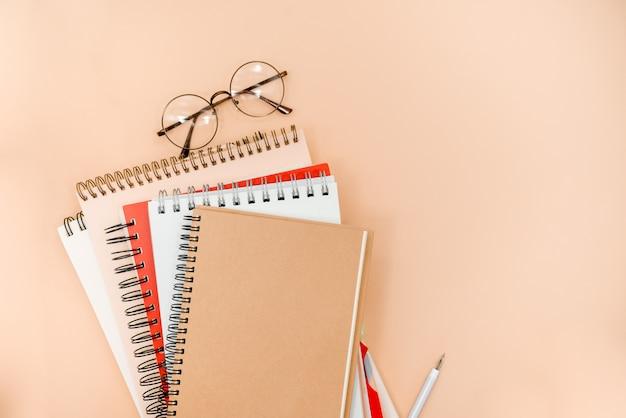 Okulary i notesy na beżowym tle streszczenie Premium Zdjęcia