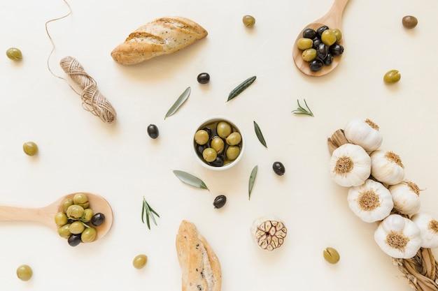 Oliwki w talerzu i łyżki z czosnkiem i chlebem Darmowe Zdjęcia