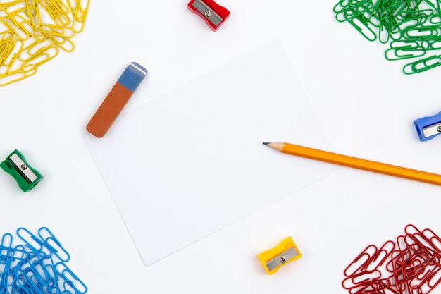 Ołówek, gumka, temperówka, spinacze do papieru leżą pod różnymi kątami arkusza na białym tle. obraz bohatera i miejsce na kopię. Premium Zdjęcia