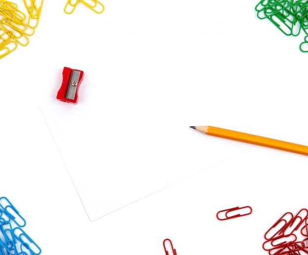 Ołówek, temperówka, spinacze do papieru leżą pod różnymi kątami arkusza na białym tle. obraz bohatera i miejsce na kopię. Premium Zdjęcia