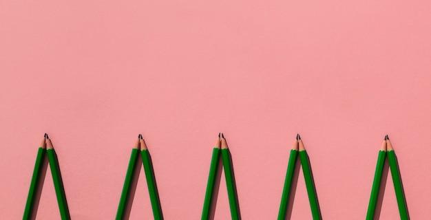 Ołówki Obramiają Na Różowym Tle Premium Zdjęcia