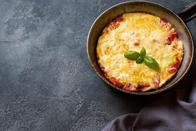 Omlet, Jajecznica Z Pomidorami I Serem Na Patelni Na Ciemnym Stole. Premium Zdjęcia