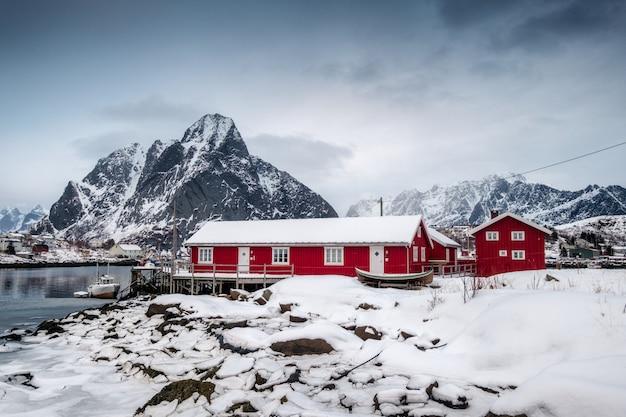 Opad śniegu na czerwień domu z schronieniem w dolinie na oceanie arktycznym Premium Zdjęcia