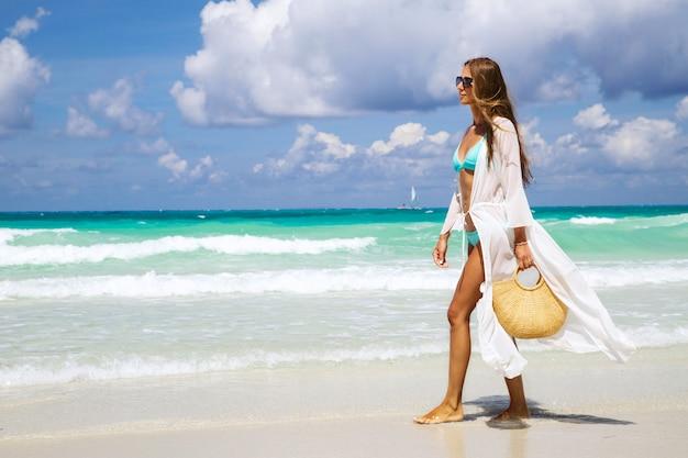 Opalona Dziewczyna W Niebieskim Bikini I Białej Tunice Trzymająca Modną Słomianą Torbę I Chodzącą Nad Morzem. Premium Zdjęcia