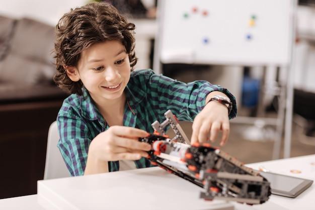 Opanowanie Nowych Umiejętności. Zachwycony, Radosny, Pomysłowy Chłopiec Siedzi W Klasie I Dotyka Urządzenia Podczas Programowania Robota Premium Zdjęcia
