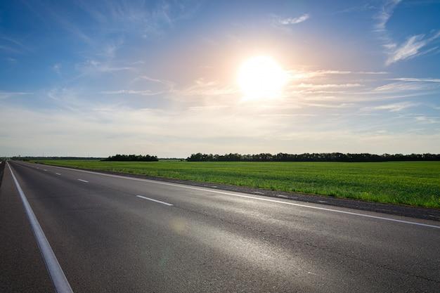 Opróżnia Asfaltową Autostradę Przeciw Jaskrawemu Słońcu Przy Zmierzchem Premium Zdjęcia