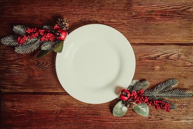 Opróżnia Półkowego Naczynie Z Przestrzenią Dla Teksta I Dwa Dekoracyjnym Jedlinowym śniadanio-lunch Na Ciemnym Drewnianym Tle. Nowy Rok I święta Bożego Narodzenia Tradycyjne Jedzenie Koncepcja. Premium Zdjęcia